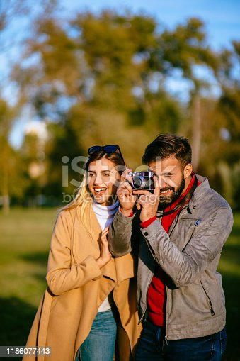 Young male photographer and his girlfriend capturing the beauty of an autumn day with a camera