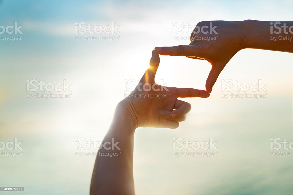 capturing the sunset by the water - Finger Frame stock photo