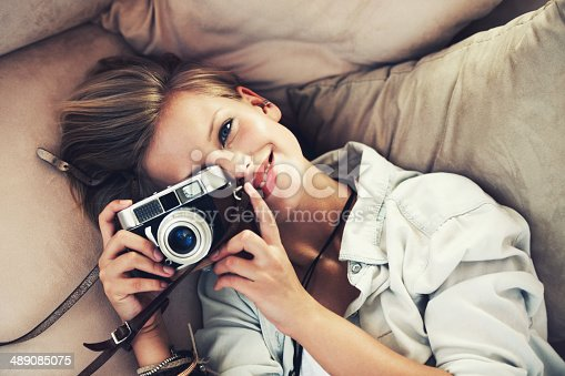 High angle view of a beautiful young woman taking a photograph while lying on a couch