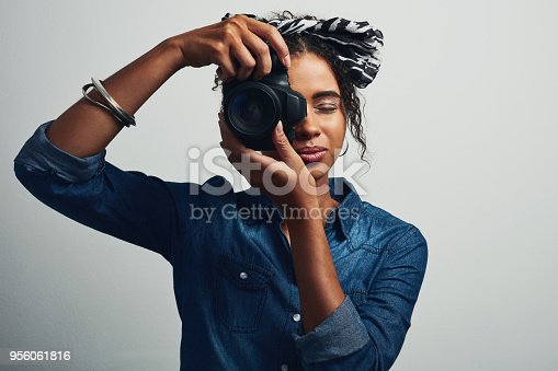 Studio shot of an attractive young woman taking a picture with a dslr camera against a grey background
