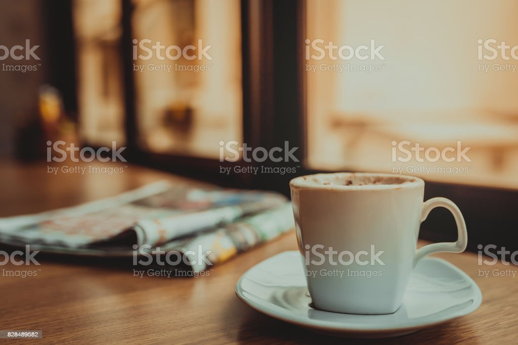 Capuccino coffee and newspaper on wooden table the windows background stock photo
