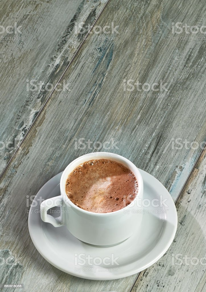 Capuccino in porcelain cup and white plate on vintage table background royalty-free stock photo