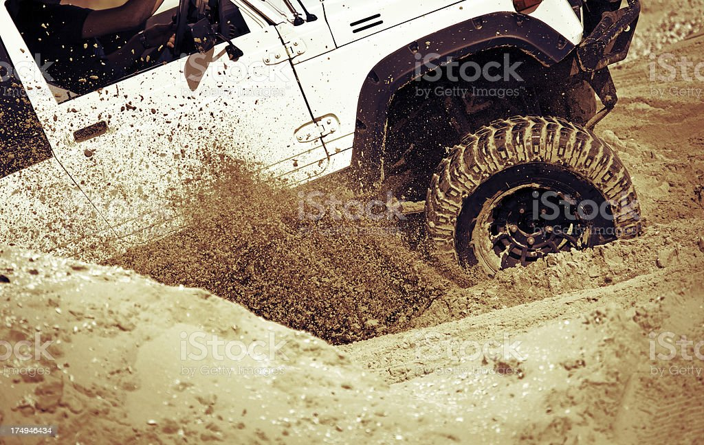 car accelerating on sand stock photo