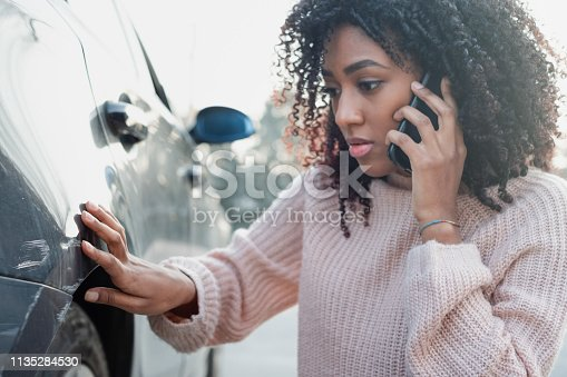 Black oman making a phone call after having a car crash