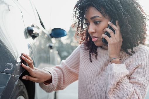 istock Car accident and black woman calling help 1135284530