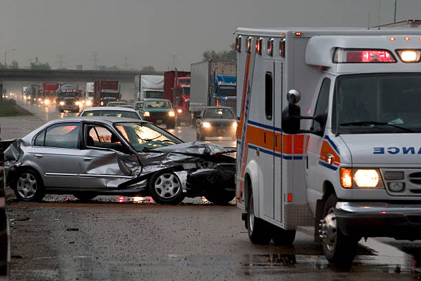 Car  Accident  Crash Car crash on major highway during rainfall at night. Ambulance in foreground and police car in background. crash stock pictures, royalty-free photos & images