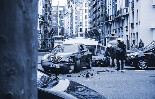684793794 istock photo Car accident on Paris street between luxury limousine Lancia Thesis and scooter 1003368312