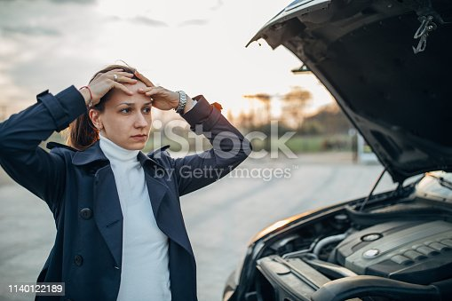 Young, stressed woman is standing next to her broken car and holding her head.