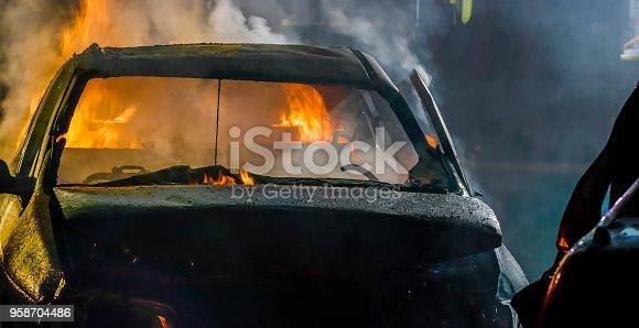 Crashed car burning at night.