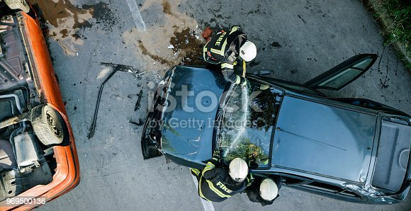 Firefighters using a glass cutter to cut car windscreen after accident.