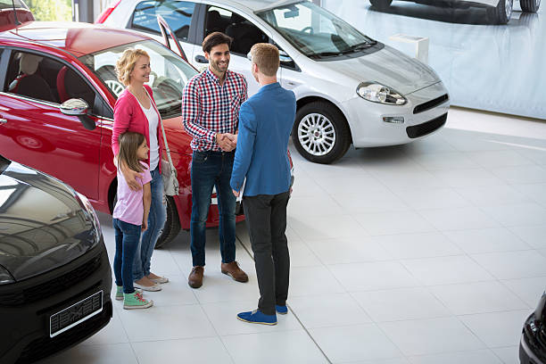 car agent congratulate the family car agent handshake with his daddy and congratulate the family on buying car car salesperson stock pictures, royalty-free photos & images