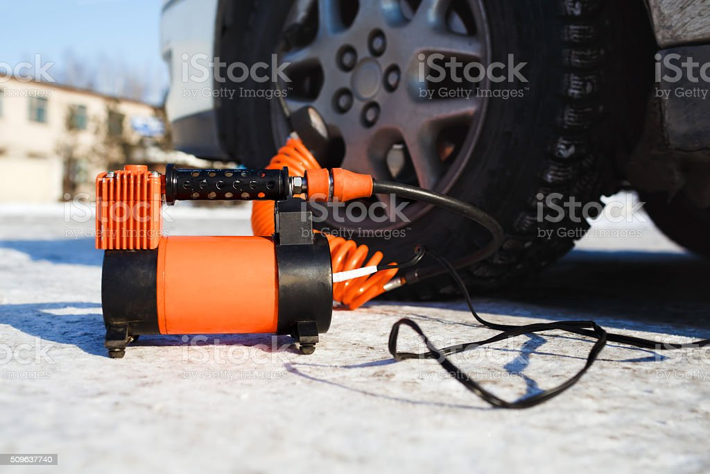 Car air compressor in working position at snow. Self-inflating stock photo