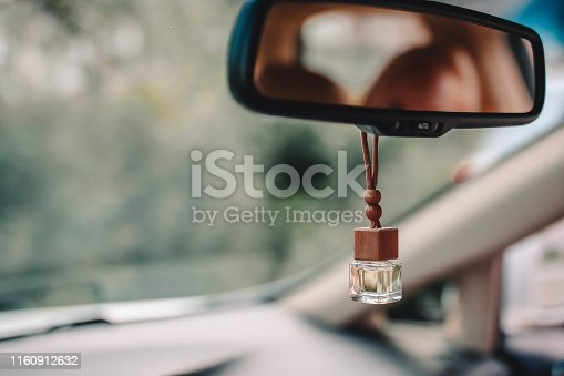 Car air perfume freshener inside the car with blurred green background. Little glass bottle with wooden lid and yellow aromatic liquid automobile freshener on car mirror.