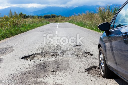 istock car and cracked asphalt with holes 928244014