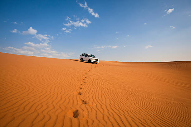 4WD car and footprints in the desert stock photo