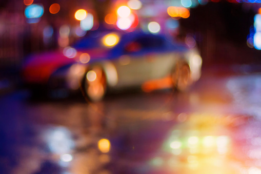 Car and passersby at night on a city street. Blurred background.