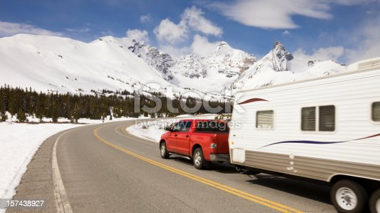 Pickup truck and travel trailer passing by on a highway in the mountains.