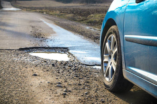 Car and winter pothole on open road stock photo