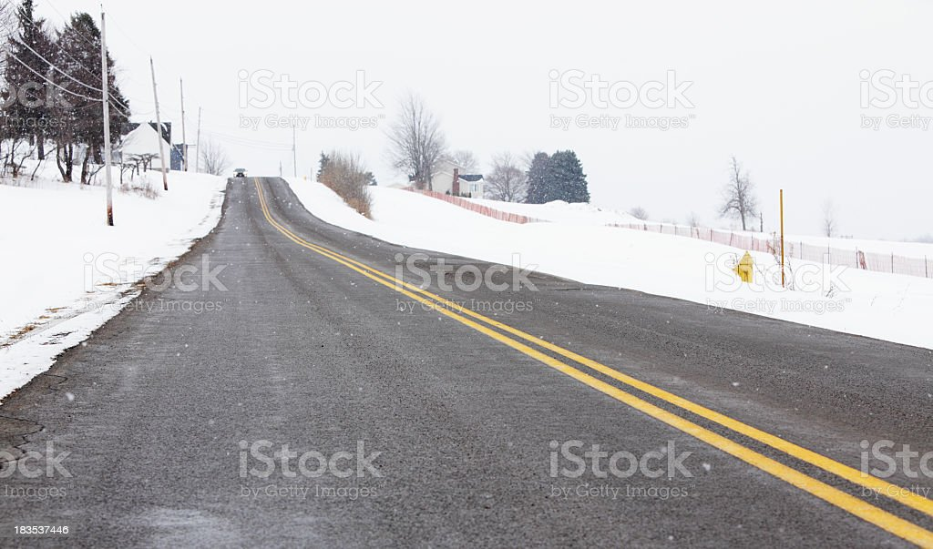 Car Approaching on Rural Winter Road Highway royalty-free stock photo