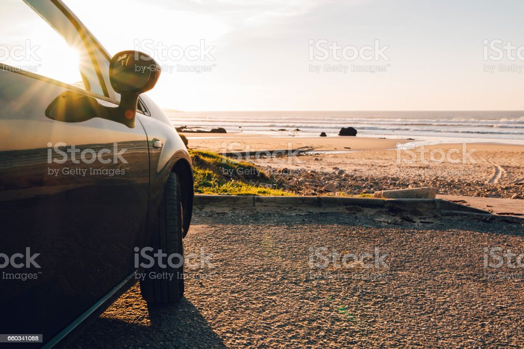 Car at beach at sunset stock photo