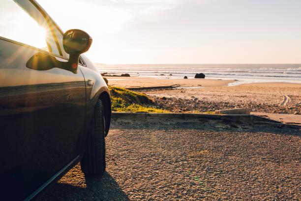 Car at beach at sunset stock photo