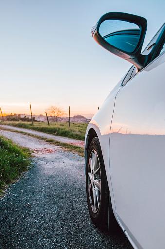 Car at countryside road at sunset