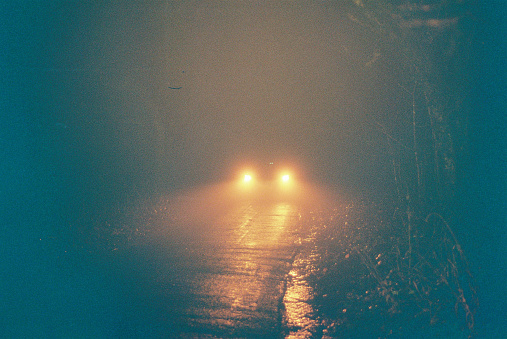 Rain and mist as a car drives down a wooded country lane, 35mm Lomography Redscale film.