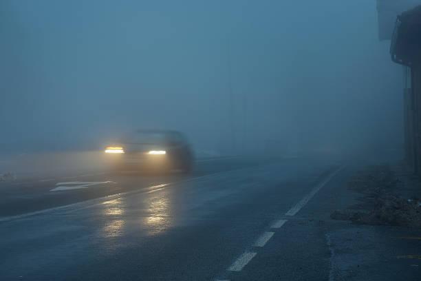 coche por la noche en mojado y resbaloso camino niebla - foto de stock