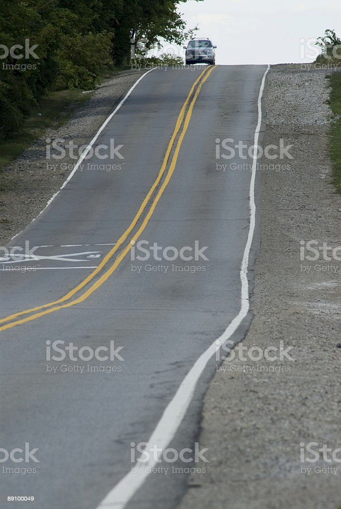 Car atop hill on rural road royalty-free stock photo