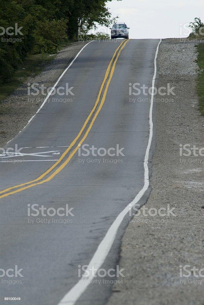 Coche en la cima de la colina sobre rural road foto de stock libre de derechos