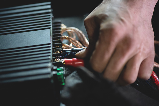 Auto electrician is connecting a wiring to car amplifier close up.
