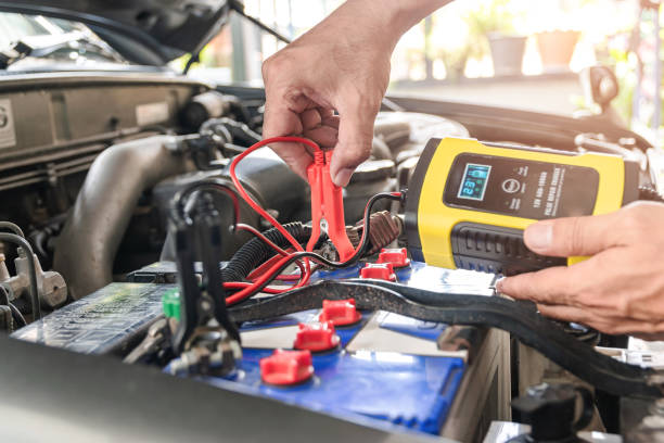 Car battery charger The car mechanic is using a voltage measuring instrument and charging the battery, the car's battery power. battery charger stock pictures, royalty-free photos & images