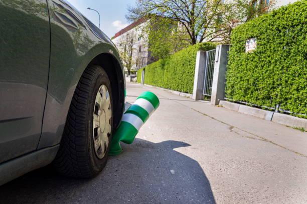 Autokennung weißer und grüner Sicherheitsverkehrsposten mit vorderer Stoßstange, falsches Parken, Kfz-Versicherung, Bußgeld, Strafkonzept – Foto
