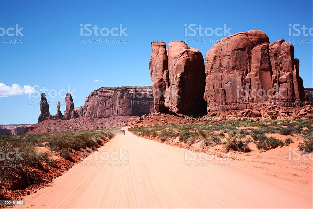 Car between Camel Butte and Three Sisters, Monument Valley stock photo