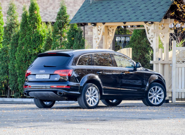 Car black Audi Q7 in the parking lot near the fence. City crossover from audi. stock photo