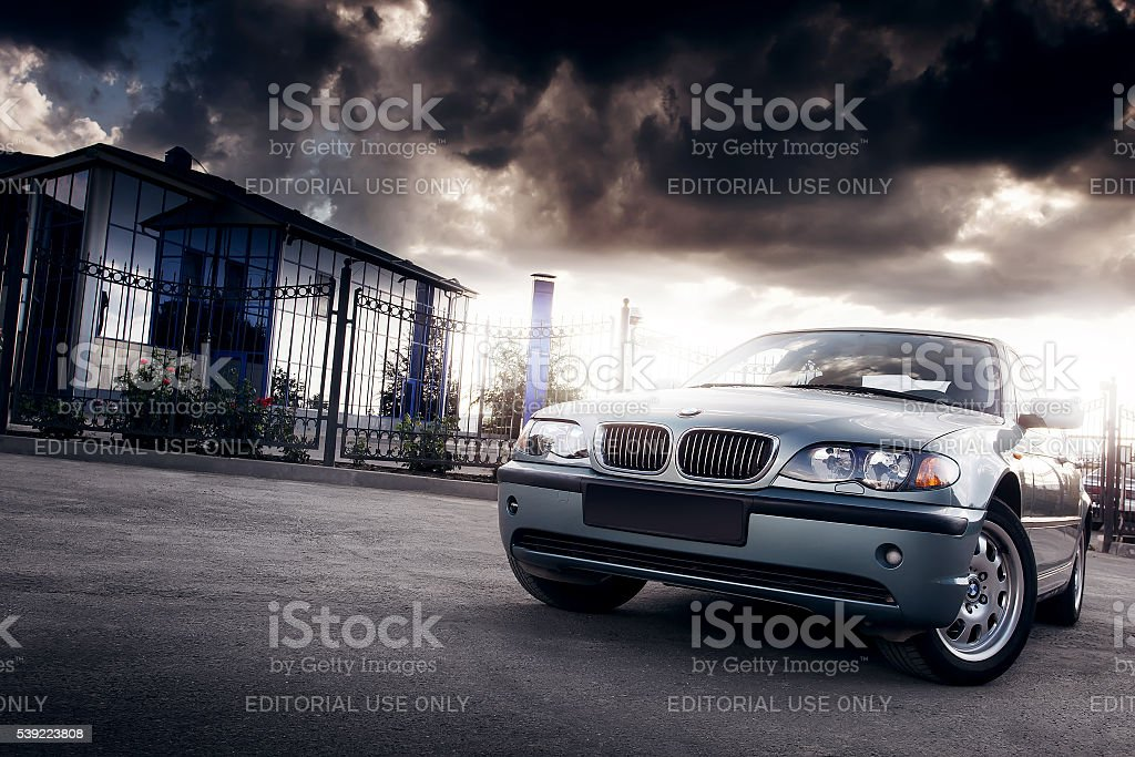 Car BMW E46 stay in the city at sunset Saratov, Russia - August 20, 2014 - Car BMW E46 stay in the city near mirror building at cloudy sunset Asphalt Stock Photo