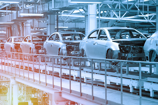 Empty car bodies are on production line. Automotive production line. Blue tone. Blue tint