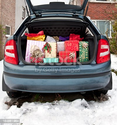 A hatchback car with its boot/trunk stuffed full of Christmas presents prior to visiting relatives on a snowy Christmas day.