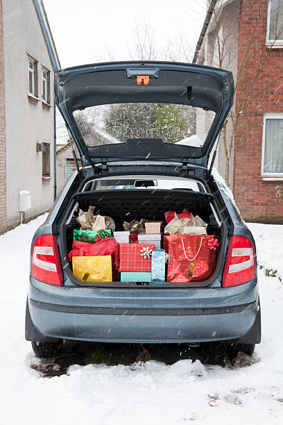 Car boot, filled with Christmas presents, snow underfoot; snowing