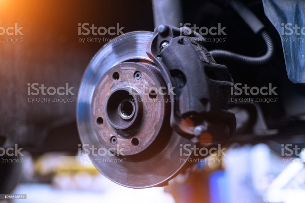 Car brake disk and caliper close up without wheel in cold colors with beautiful backlight Car brake disk and caliper close up without wheel in cold colors with beautiful backlight Brake Stock Photo