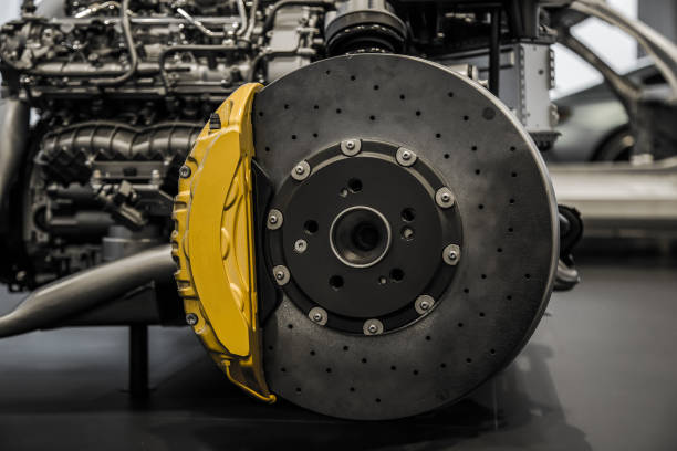 Car braking system Automobile braking system. Ceramic carbon disk with perforation, ventilation and yellow calipers. padding stock pictures, royalty-free photos & images