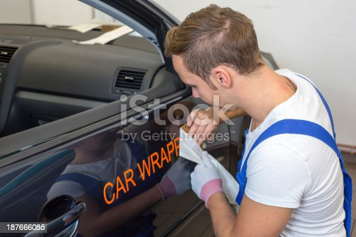 istock A car branding specialist applying a logo to a car 187666085