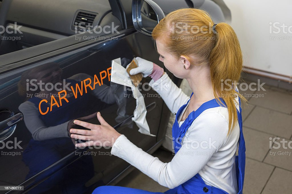 Car branding specialist puts logo with wrapping film on auto stock photo