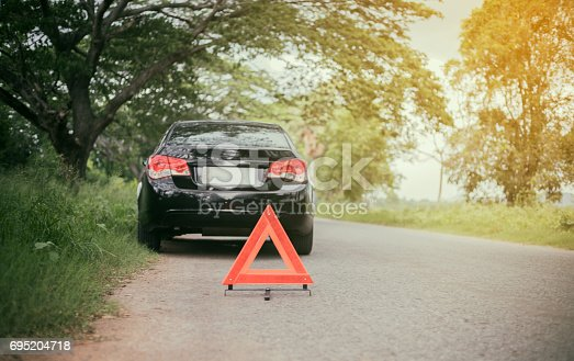 istock A car breakdown with Red triangle of a car on the road 695204718