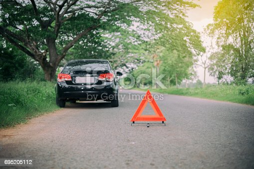 istock A car breakdown with Red triangle of a car on the road 695205112