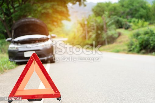 car broken down on the road with emergency help sign. car break down trouble on road, traffic warning triangle sign on asphalt road. Emergency stop concept. Red triangle of a car on nature road.Broken car in country mountain road. Damage car with reflective triangle .