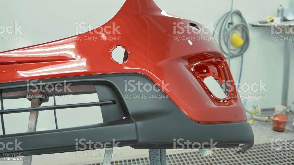 Car bumper after painting in a cars spray booth. Vehicle cherry color bumper stock photo