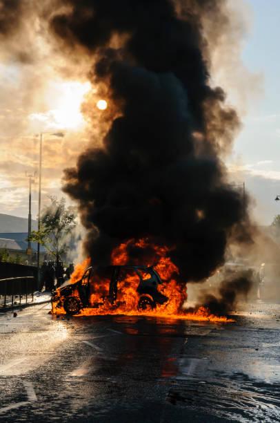 Ein Auto brennt mitten auf einer Straße, mit viel schwarzem Rauch während eines Aufruhrs – Foto