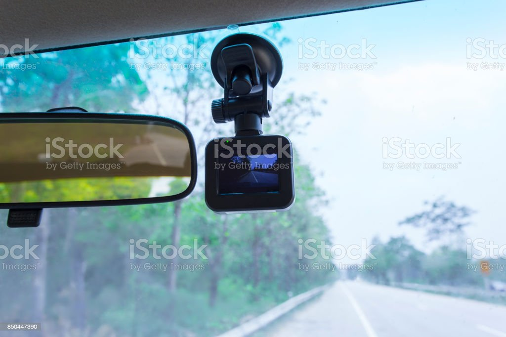 Car camera installed on wind shield of vehicle which can be truck or car of driver whose on the road trip or during traveling on the high way. The camera can be record the video for evidence accident. stock photo