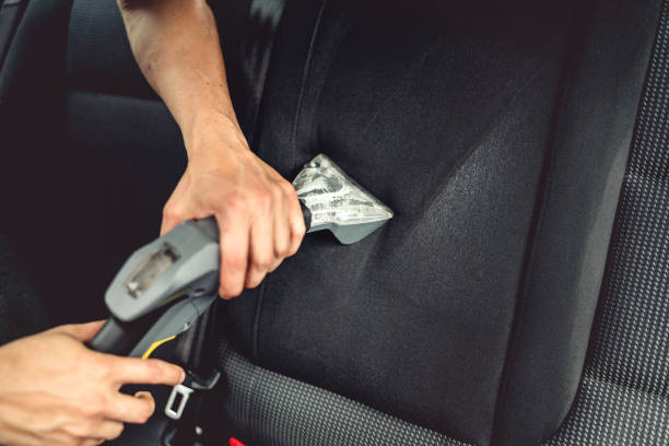 Car care concept, professional steam vacuuming the upholstery of back seats stock photo
